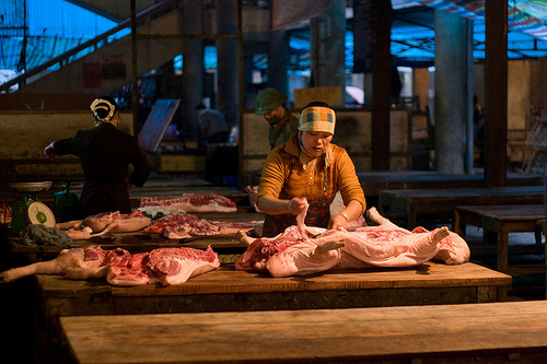 At the Sunday market in Sapa, northern Vietnam, women butcher hogs slaughtered outside of town but still steaming when they start working on them at the market (image via Flickr/Kurt Johnson).